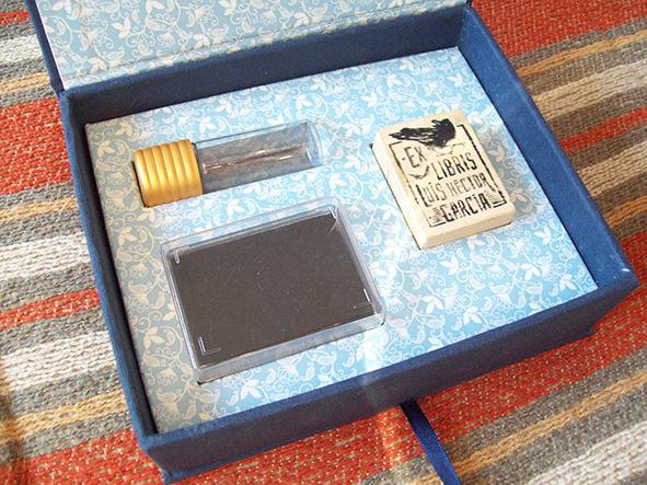 Interior con cunas para objetos del kit. Almohadilla para sello, frasco de tinta y sello.